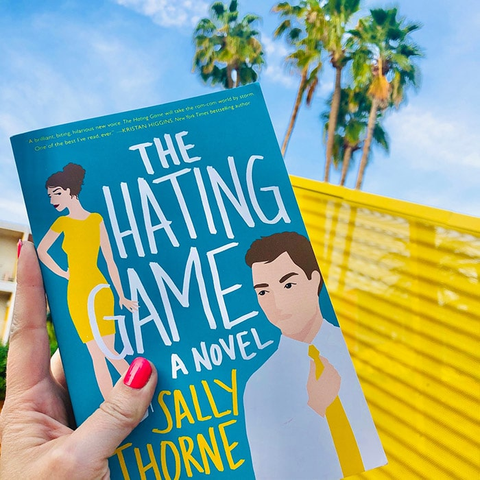The Hating Game novel cover in front of palm trees and blue skies