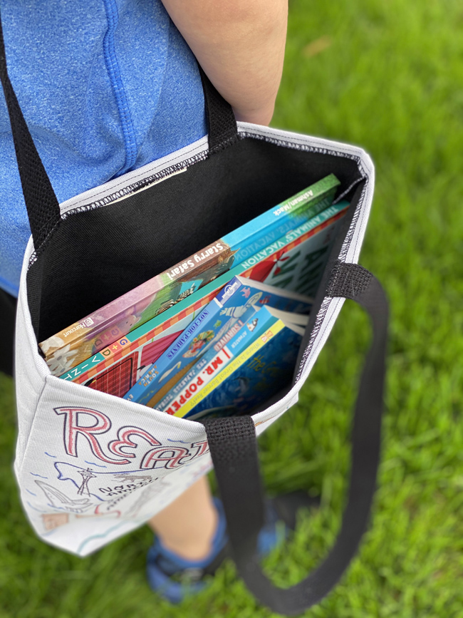 child with library book tote full of books