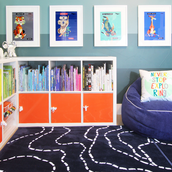 Corner bookshelf in kids' room with books organized by color