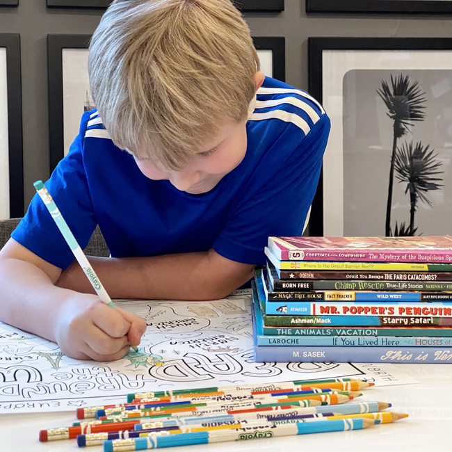 Boy coloring large world map poster with colored pencils and stack of books