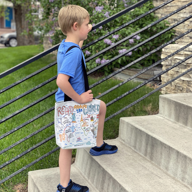 boy carrying illustrated world map library tote bag